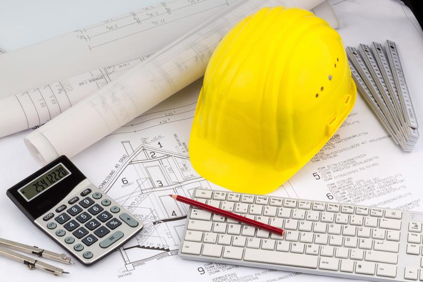 Ein Bauplan eines Architekten mit dem Bauhelm eines Bauarbeiters. Symbolfoto für Finanzierung und Planung eines neuen Hauses.